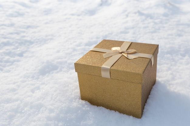 Золотая подарочная коробка на снежном ландшафте смычка. вид сверху, плоская планировка. концепция покупок