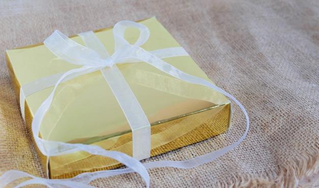 茶色の袋に白いリボンと金のギフトボックス