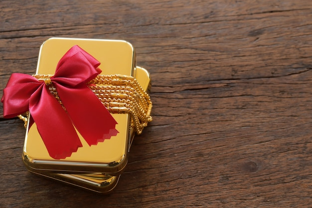 Gold gift boxes with gold necklace and ribbon on brown wooden background