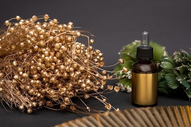 Gold glass bottle with cosmetics on a black background with bouquet of golden dried flowers. dropper with cosmetic oil or serum. anti-aging facial skin care