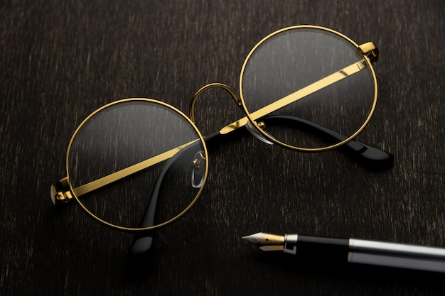 Gold glasses, pen on a dark wooden background..