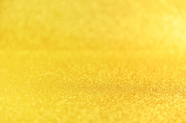 Gold glitter close up background. sparkling yellow defocused backdrop.
