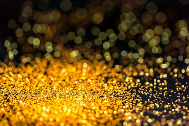 Gold glitter powder sparkling on black background.