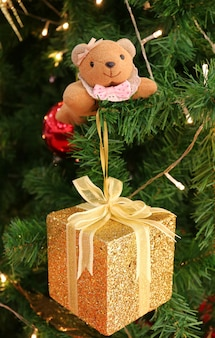 Gold glitter square mini gift box with a cute squirrel soft toy on christmas tree
