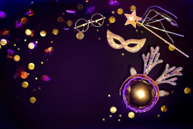 Gold glittering masquerade accessories on a black background with confetti