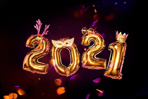 Gold glittering numbers 2021 on black background in carnival accessories, new year party concept. confetti is flying.