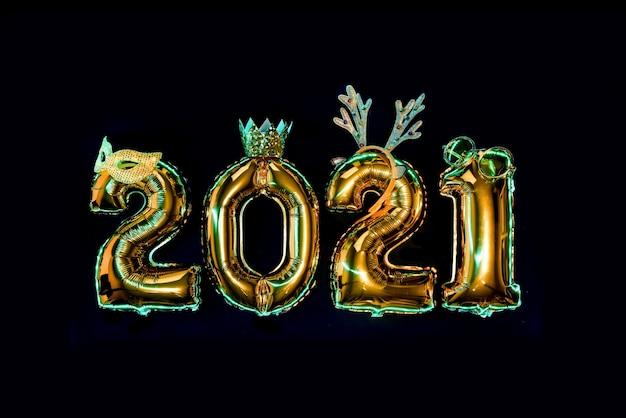 Золотые сверкающие цифры 2021 года на черном фоне в карнавальных аксессуарах