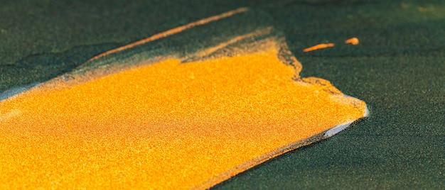ゴールドのきらびやかなスミア。抽象的なペイントテクスチャ