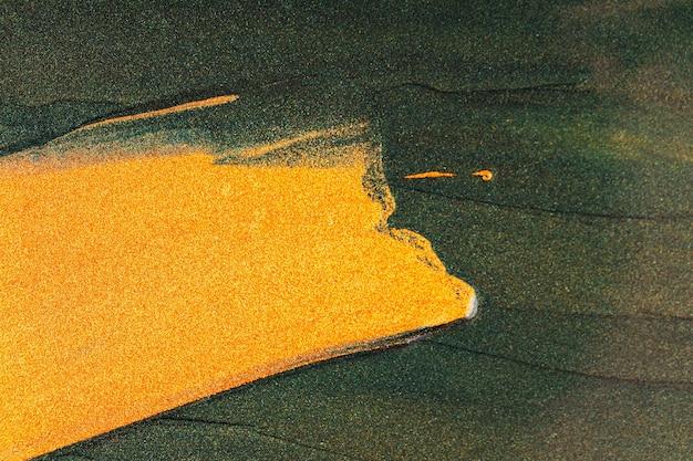 濃い緑色の背景にゴールドのきらびやかな塗抹標本。抽象的なペイントテクスチャ