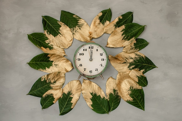 Gold and green painted leaves on circle frame with clock
