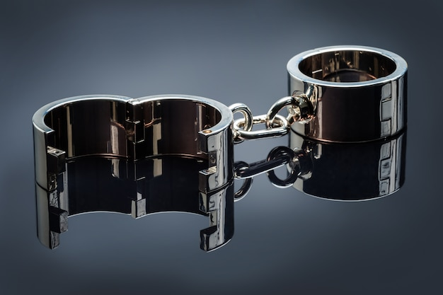 Gold handcuffs lie on a gray metal mirror surface