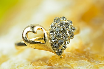 Gold heart shape ring on marble stone background