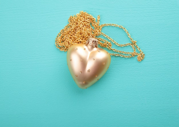 Gold heart with gold chain on the wood texture
