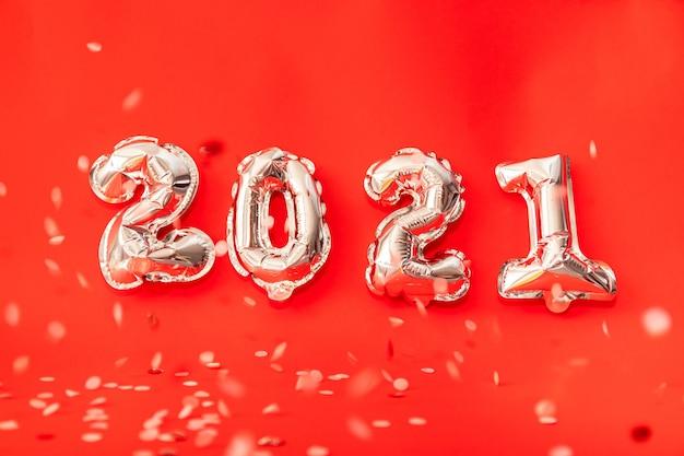金のヘリウム風船が新年あけましておめでとうございます2021年を祝福、赤い背景に分離されたクリスマスのお祝いの装飾を形成