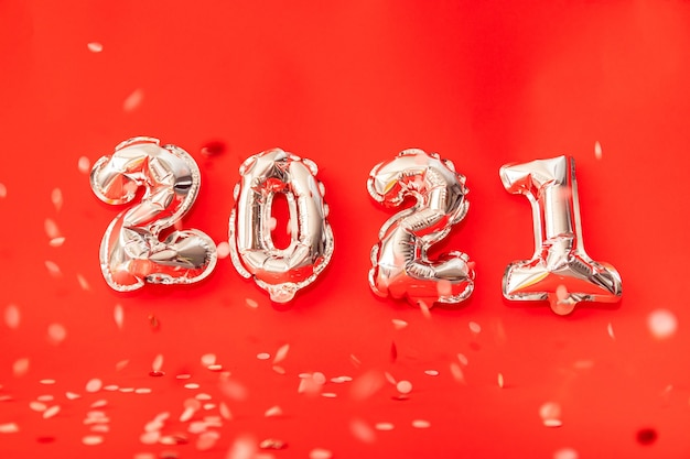 Gold helium balloons forming happy new year 2021 congratulation, christmas celebration decoration isolated on red background