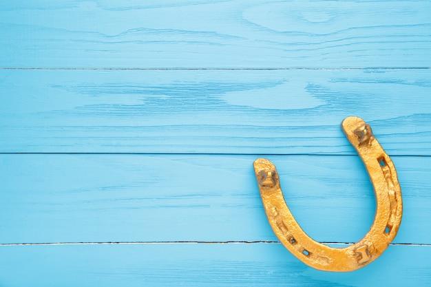 青い背景の上の金の馬蹄形。聖パトリックの日。上面図