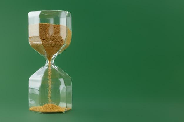 진한 녹색 종이에 금 모래 시계