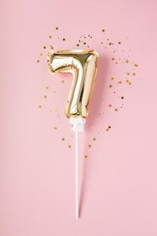 Золотая надувная цифра 7 на палочке золотого конфетти на розовом фоне. понятие праздника, дня рождения, юбилея.