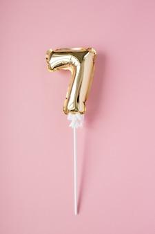 Золотая надувная цифра 7 на палочке на розовом фоне. понятие праздника, дня рождения, юбилея.