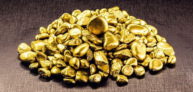 Gold on isolated black background, gold stones, rare stones mining concept