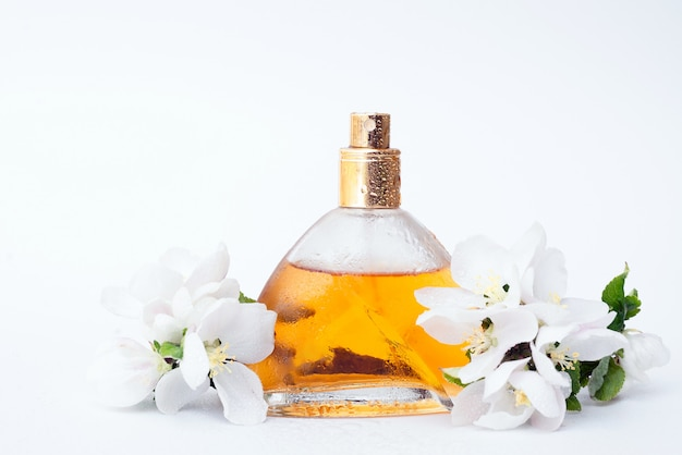 Gold jar of female perfumes on white background with spring faded flowers and drops of water