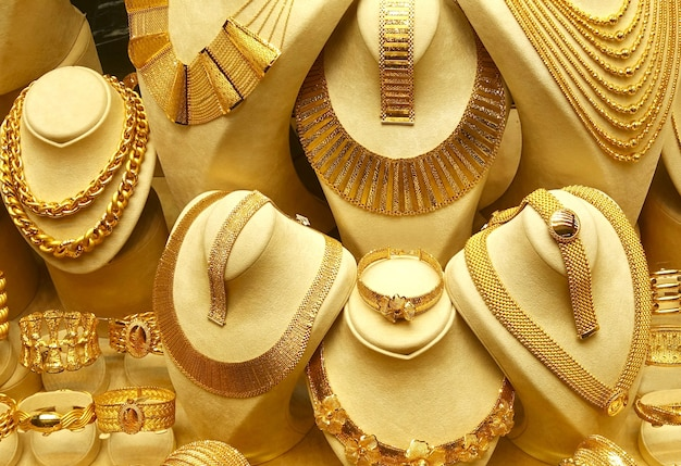 Gold jewelry necklaces and bracelets on stands