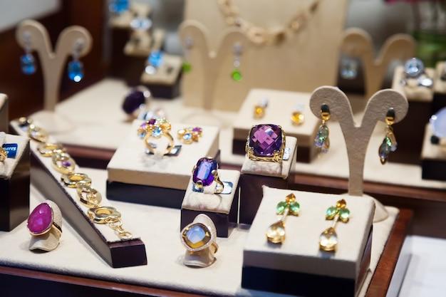 Золотые украшения с драгоценными камнями на витрине
