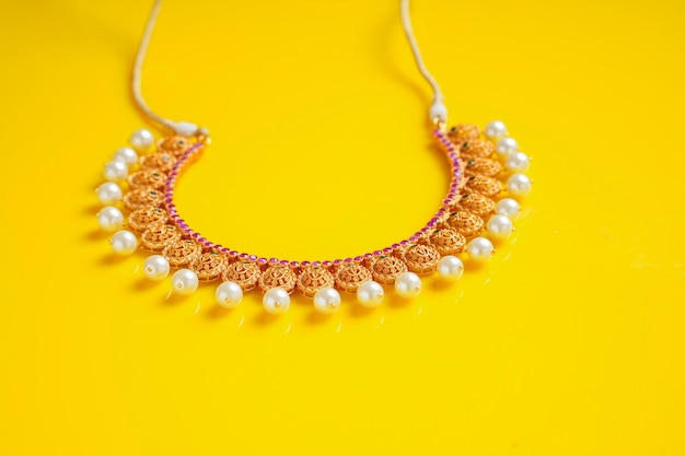Gold jewelry on yellow background