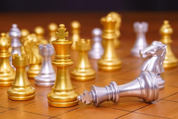 金の王のチェスの駒とさまざまなチェスの駒が木製のチェス盤の上に立つ、戦略のリーダーシップゲームの概念