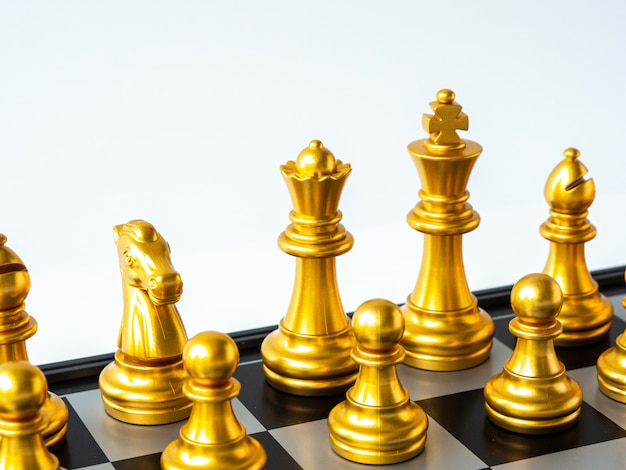 Gold king chess piece face and the golden team on the chessboard