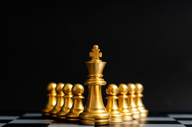 Gold king chess piece stand in front of pawn on black (concept of leadership, management)