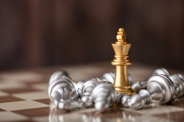 Gold king standing in the midst of falling chess on board