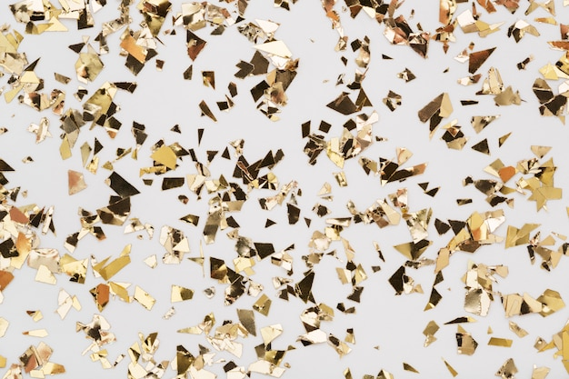 Конфетти сусального золота на белом.