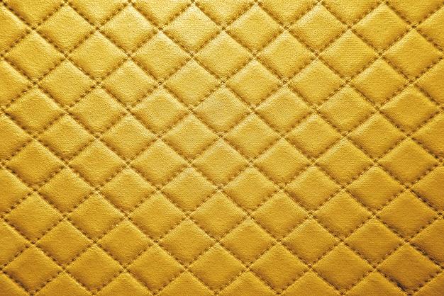 縫い目の背景とゴールドの革の質感