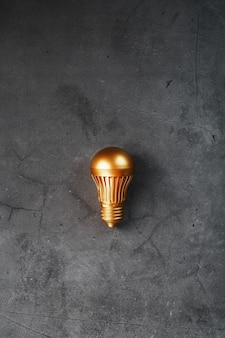 Gold light bulb on a black textured surface
