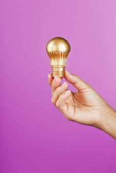 ピンクの女性の手に金の電球