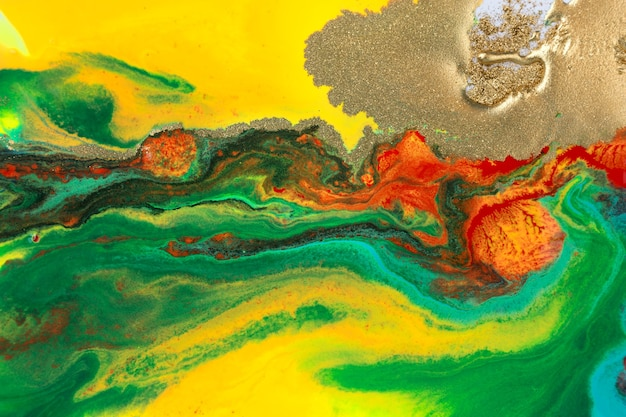 Gold liquid spots on rainbow smudges of paint abstract pattern