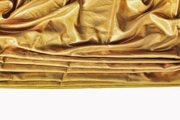 Золотая роскошная атласная ткань текстуры для фона