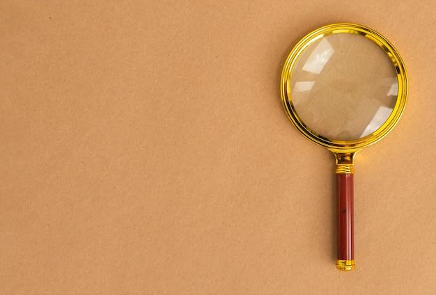 갈색 판지 배경 위에 골드 돋보기 렌즈입니다. 텍스트 복사 공간이있는 검색 도구입니다.