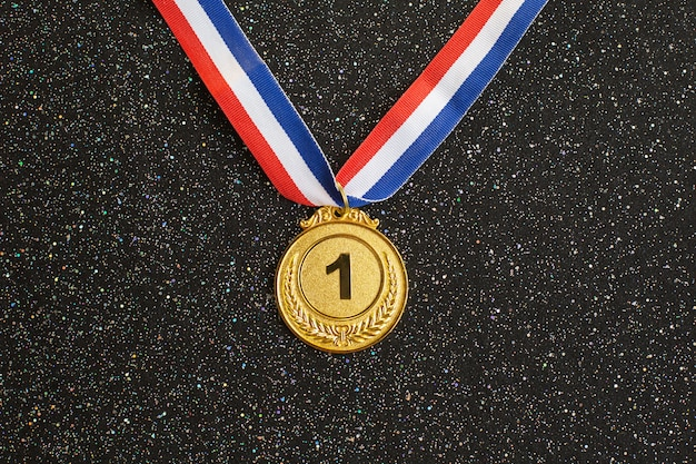 Gold medal 1 place with a ribbon on a black glitter