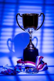 Золотая медаль и чемпионский кубок, шприц с допингом, таблетка-таблетка и флакон с запрещенным веществом с подсветкой и тенями занавеса, проникающего через окно в ночное время. концепция допинга