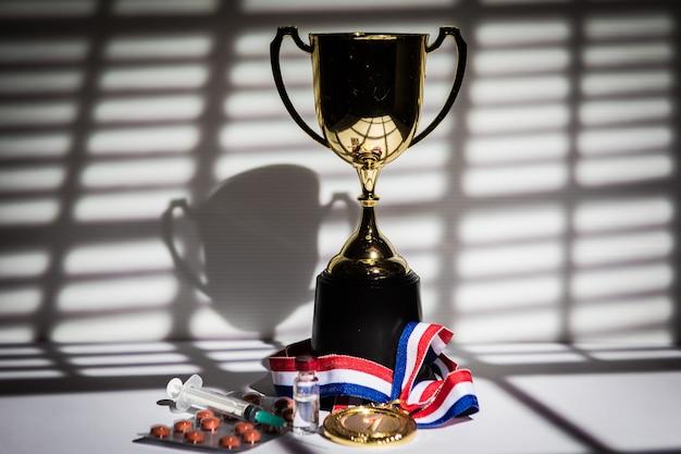 금메달과 챔피언의 컵, 도핑 물질이 있는 주사기, 알약 정제, 금지 물질이 있는 유리병, 창문을 통해 들어오는 커튼의 빛과 그림자. 스포츠 및 도핑 개념