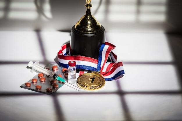 Золотая медаль и чемпионский кубок, шприц с допингом, таблетка-таблетка и флакон с запрещенным веществом с огнями и тенями занавеса, проникающего через окно. концепция спорта и допинга