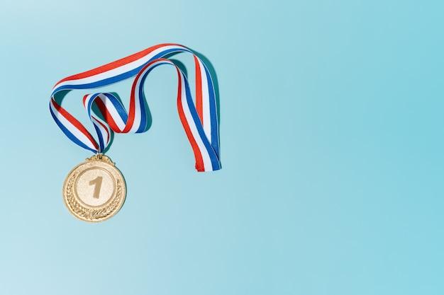 Золотая медаль на синем фоне. концепция награды и победы. копией пространства