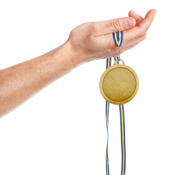 Gold medal winner in the hand. on a white wall.