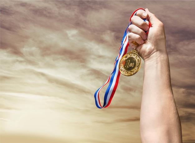 Золотая медаль с лентой в руке на фоне
