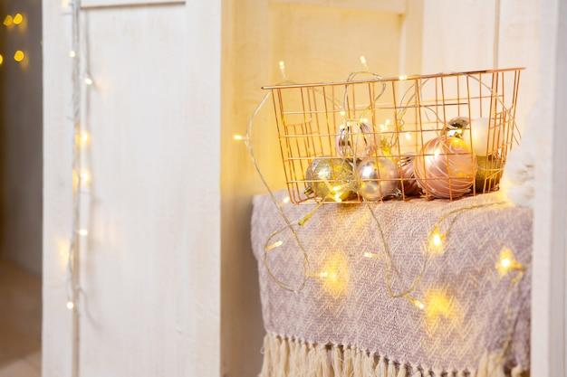 Золотая металлическая корзина на полке в деревянном шкафу или платяном шкафу гирлянда новогодние шары в корзине