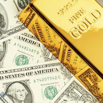 Золотой металлический слиток на поверхности долларовых купюр.