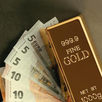 Золотой металлический слиток в слитках на поверхности банкнот евро.