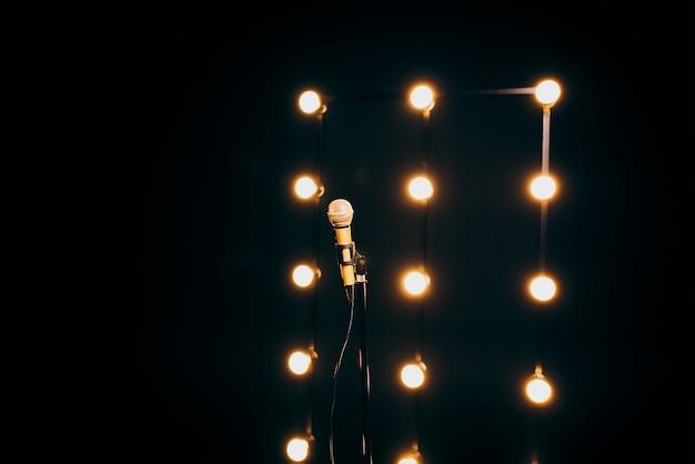 マイクスタンドの金色のマイクは、多くのライトが付いている暗い背景に立っています
